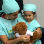 nurse and child with teddy bear